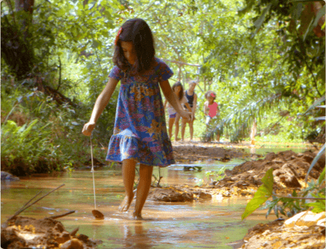 Girl in the middle of nature playing with a tree leaf while going through a puddle