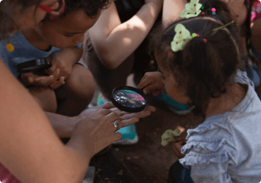 Children gathered together seeing insects with a magnifying glass