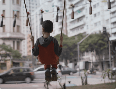 Boy sitting on the swing in an urban center